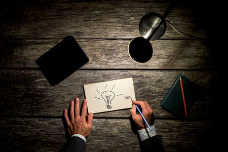Overhead view of a businessman working late at his table by the light of a desk lamp creating new ideas with light bulb drawn on paper, digital tablet and note with pen also lying on his wooden desk. Imagens