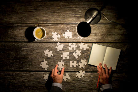 reference book: Business man brainstorming trying to find a solution staying late at the office and working by lamp light with a reference book and puzzle pieces and a stimulating cup of coffee, overhead view.