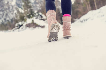 Actieve vrouw lopen weg van de camera door de winter sneeuw dragen lichtroze laarzen in het platteland, met copyspace op de voorgrond. Retro filter effect. Stockfoto