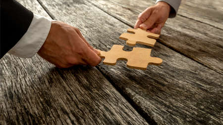 Business partnership or teamwork concept with a business people presenting a matching puzzle piece as they cooperate on finding an answer and solution, close up of their hands. Stockfoto