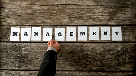 deployment: Top view of manager hand arranging ten white cards with letters on them in a line to form a word MANAGEMENT on textured antique wooden boards. Stock Photo