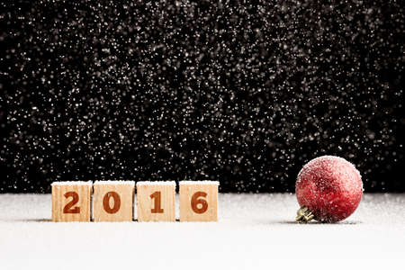 falling cubes: Four wooden cubes with 2016 sign on them laying on snowy surface with Christmas bauble next to them and gentle snowflakes falling from above.
