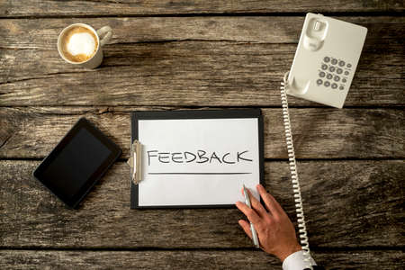 feedback: High Angle View of Feedback Concept Written on a Paper in a Clipboard, Placed on Top of a Rustic Wooden Table with Tablet Computer, Telephone and a Cup of Coffee. Stock Photo