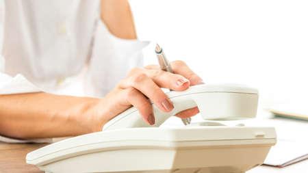 Gros plan de femme secrétaire ou par téléphone opérateur suspendu ou ramasser récepteur téléphonique blanc tout en tenant un stylo à encre.