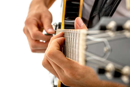 acoustic guitar: Close up oblique angle view of the fingers of a man strumming a guitar selecting the notes on the strings, over a white background.