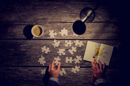 Business man working late at the office trying to find a solution in a concept with an overhead view of his desk and hands by lamp light with puzzle pieces, coffee and a light bulb for bright ideas.