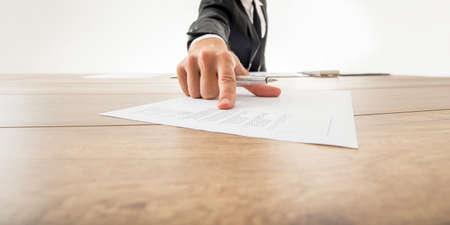 revisando documentos: Asesor de negocios que muestra a un pedazo de documento con datos estadísticos empujándolo hacia usted en el escritorio de oficina de madera. Foto de archivo