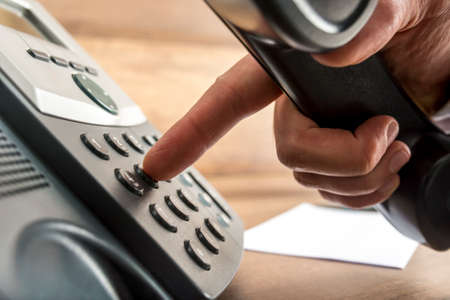 Closeup of male hand dialing a telephone number on black landline phone in a global communication concept. Standard-Bild