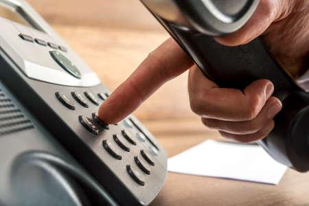 Primo piano della mano maschile che compone un numero di telefono a telefono fisso nero in un concetto di comunicazione globale. Archivio Fotografico
