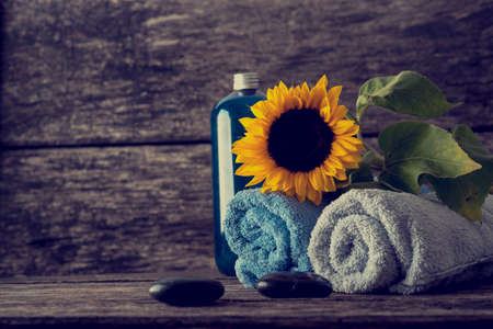 shower gel: Care for personal hygiene concept - beautiful blooming sunflower on two rolled towels with shower gel and black zen stones next to them on a textured rustic wooden background. Stock Photo