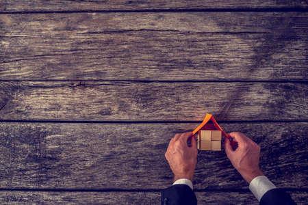 Visie van nieuw huis - bovenaanzicht van architect of makelaar het plaatsen van een dak op de top van huisminiatuur gemaakt van vele houten kubussen op gestructureerde houten planken. Stockfoto