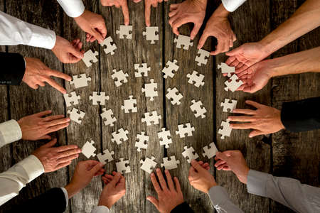 challenges: Teamwork Concept - High Angle View of Businessmen Hands Forming Circle and Holding Puzzle Pieces on Top of a Rustic Wooden Table.