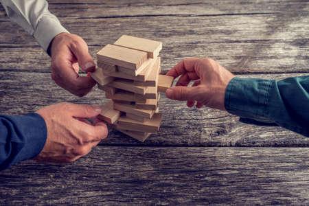Drei Geschäftsmänner Hände spielen Wooden Turm Spiel oben auf einem rustikalen Holztisch. Konzeptionelle von Teamwork, Strategie und Vision.