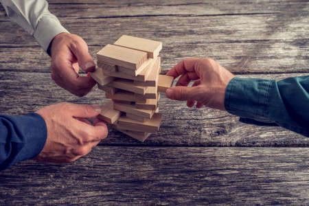 teamwork  together: Three Businessmen Hands Playing Wooden Tower Game on Top of a Rustic Wooden Table. Conceptual of Teamwork, Strategy and Vision.