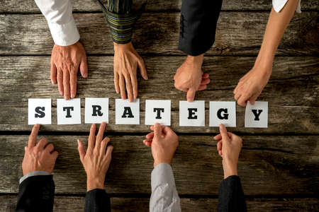 Top view of eight business people assembling the word STRATEGY while each holding one card with letter on it. Conceptual of cooperation in finding the best approach to develop business and company. Standard-Bild