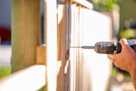 야외 가까운 그의 손과 DIY 개념의 도구들로, 수직 판자를 연결하는 구멍을 드릴 휴대용 전기 드릴을 사용하여 나무 울타리를 세우는 사람 (남자).