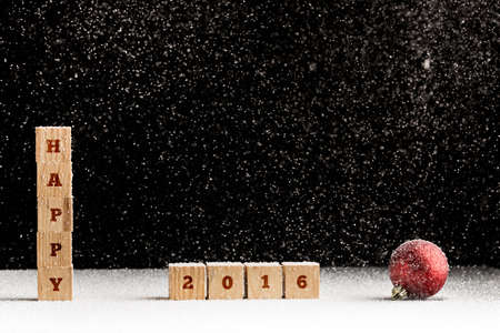 out of date: New Year 2016 background with falling snow and a red Christmas bauble with the word Happy spelled out on stacked wooden blocks with the date 2016 alongside over black with copyspace for your greeting.