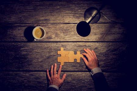 Bovenaanzicht van zakenman werken laat op de avond aan zijn rustieke bureau om eindelijk kwam tot een conclusie of een oplossing over de toekomst van zijn bedrijf door het samenvoegen van twee bijpassende puzzelstukjes.