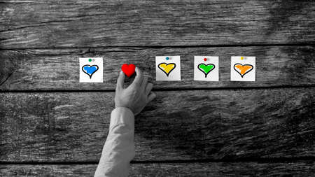 lustful: High Angle View of a Man Hand Arranging Colourful Hearts in Horizontal Orientation on Top of a Rustic Wooden Table, Selective Colours of the Hearts in a Greyscale Image Conceptual of Love.