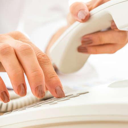 Close-up van de vrouwelijke telefoon operator kiezen van een telefoonnummer maken een belangrijk zakelijk gesprek op een witte telefoon.