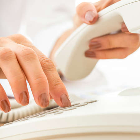 Closeup of female telephone operator dialing a phone number making an important business call on white telephone. Banco de Imagens