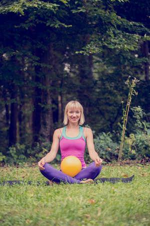 mente: Vista frontal de la mujer joven rubia haciendo una posici�n de loto en la sentada con las piernas cruzadas con el ejercicio pelota amarilla en su regazo fuera en la naturaleza verde. Conceptual de la mente por completo, cuerpo y esp�ritu ejercicio.