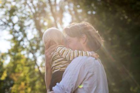 children love: Tender loving moment between a young father and his toddler son - dad holding the boy in his arms hugging him happily in a beautiful nature with sunlight.