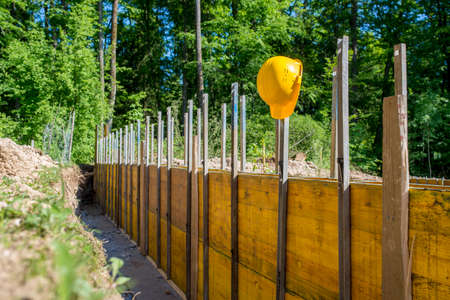 forested: Yellow hardhat hanging  from supported wooden panels on a building site in a construction and building concept, outdoors in a forested area.
