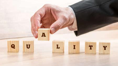 business services: Businessman assembling the word Quality with seven wooden cubes with letters on them. Conceptual of business services and trade.