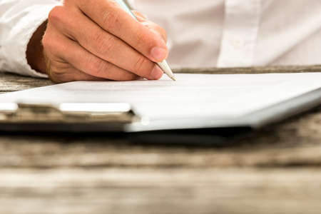 entity: Closeup low angle view of male hand signing subscription form, legal document or business contract. Focus to the tip of the pen. Stock Photo