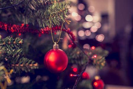 navidad elegante: Primer de la chuchería roja colgando de un árbol de Navidad decorado. Efecto de filtro retro.