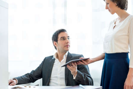 secretaria: Secretaria de negocios que da una tableta digital a su superior en un entorno de oficina blanco.
