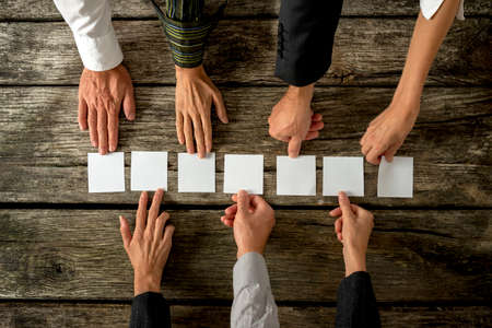 salespeople: Seven hands of business people placing seven blank white cards in a row on a wooden desk. Stock Photo