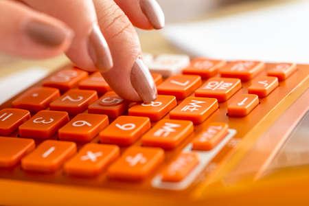 女性会計士の会計、研究または教育コンセプトでオレンジ色の電卓の数 8 を押すことのクローズ アップ。