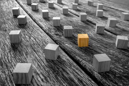 Conceptuele Brown houten blok omringd door andere blokken in zwart-wit op de top van een rustieke tafel.
