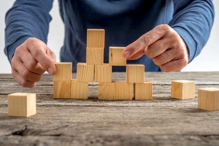 Close-up van de mens in elkaar zetten van een toren met behulp van houten kubussen op de top van een rustieke tafel. Stockfoto