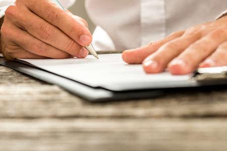 Inquadratura dal basso di sesso maschile firma del contratto a mano o sotto forma di sottoscrizione con una penna su una scrivania di legno rustico.
