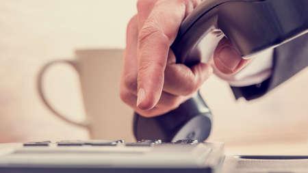 Imagen de estilo retro de la mano masculina marcar un número de teléfono en un teléfono negro con la taza de café en segundo plano. Foto de archivo - 45838863