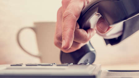 conference call: Retro image of male hand dialing a telephone number on a black phone with cup of coffee in background.
