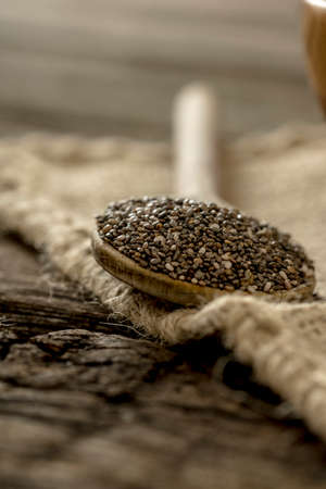 burlap sac: Wooden spoon full of healthy nutritious chia seeds on a burlap sac on a rustic wooden desk. Stock Photo