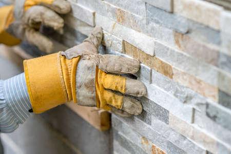 deitado: Close up do trabalhador manual em luvas de proteção empurrando o azulejo no cimento na parede enquanto telha uma parede com azulejos l em um conceito DIY, reforma ou construção.