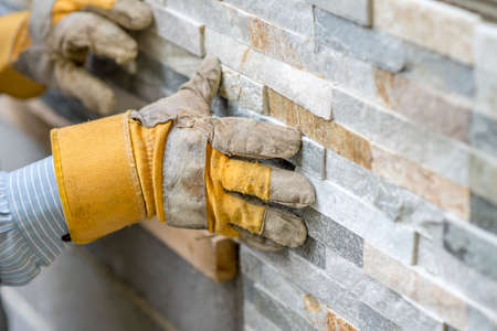 protección: Primer plano de trabajador manual en guantes de protección que empujan el mosaico en el cemento en la pared, mientras que las baldosas de una pared con azulejos ornamentales l en un concepto de bricolaje, renovación o construcción. Foto de archivo