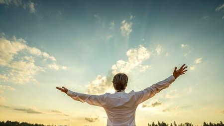 Riuscito uomo in elegante camicia bianca in piedi con le spalle alla telecamera con il suo braccio si diffuse verso bel cielo maestoso sera mentre si celebra il suo successo e la prosperità. Archivio Fotografico