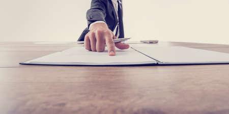 contrato de trabajo: Vista frontal del empleador que apunta a un contrato donde firmar, efecto vintage imagen de tonos.