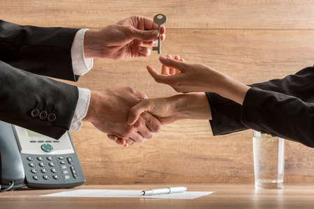 Succesvolle zakelijke deal - makelaar en nieuwe vrouwelijke huiseigenaar uitwisselen huissleutel terwijl handen schudden over een contract van de huis verkoop.