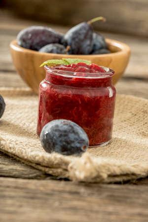 burlap sac: Jar of homemade plum jam with wooden bowl of juicy ripe fresh plums in background sitting on burlap sac. Stock Photo