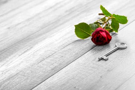 로맨스: Selective colour of the rose in a greyscale image in a conceptual image of romance, love, proposal and devotion with beautiful blooming red rose and key on wooden table with copy space.