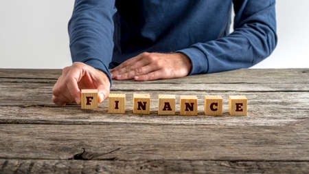 financial planner: Front view of man in blue shirt assembling the word Finance with seven wooden cubes with letters on them on a rustic wooden desk. Stock Photo