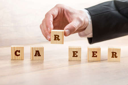 self realization: Career adviser assembling the word career with six wooden cubes  in a conceptual image of personal guidance towards self realization. Stock Photo
