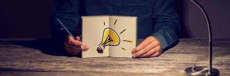 newness: Businessman or student showing his working notebook with a hand drawn light bulb. Conceptual of innovation, idea and vision for personal and business progress. Stock Photo